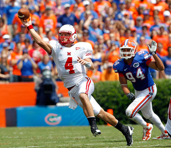 GAINESVILLE, FL - SEPTEMBER 04:  Zac Dysert #4 of the Miami University RedHawks attempts a pass while being pressured by Justin Trattou #94 of the Florida Gators at Ben Hill Griffin Stadium on September 4, 2010 in Gainesville, Florida.  (Photo by Sam Gree