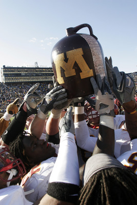 ANN ARBOR, MI - OCTOBER 8:  Minnesota players celebrate with the 'Little Brown Jug' trophy after defeating Michigan at Michigan Stadium October 8, 2005 in Ann Arbor, Michigan. Minnesota kicked a last-second field goal to win the game, 23-20.  (Photo by To