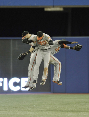 TORONTO, CANADA - JULY 26:  Nolan Reimold #14, Nick Markakis #21 and Adam Jones #10 of the Baltimore Orioles celebrate the teams win over the Toronto Blue Jays during MLB game action July 26, 2011 at Rogers Centre in Toronto, Ontario, Canada. (Photo by Br