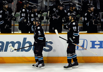 SAN JOSE, CA - MAY 22:  Ian White #9 and Ryane Clowe #29 of the San Jose Sharks skate by the Sharks bench to celebrate with teammates after a goal by Clowe in the third period in Game Four of the Western Conference Finals during the 2011 Stanley Cup Playo