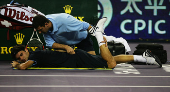 SHANGHAI, CHINA - NOVEMBER 14:  Roger Federer of Switzerland receives treatment from ATP trainer Hugo Gravil during his round robin match against Andy Murray of Great Britain in the Tennis Masters Cup held at Qi Zhong Stadium on November 14, 2008 in Shang