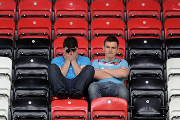 WIGAN, ENGLAND - MAY 15:  West Ham United fans look dejected following their relegation at the end of the Barclays Premier League match between Wigan Athletic and West Ham United at the DW Stadium on May 15, 2011 in Wigan, England.  (Photo by Chris Brunsk