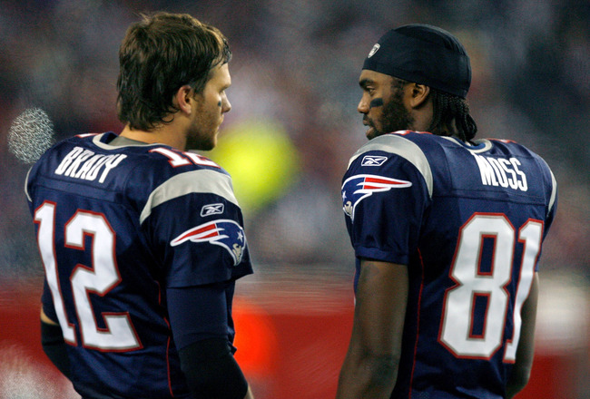 FOXBORO, MA - DECEMBER 23: Randy Moss #81 and Tom Brady #12 of the New England Patriots talk on the sidelines against the Miami Dolphins at Gillette Stadium on December 23, 2007 in Foxboro, Massachusetts. The Patriots won 28-7. (Photo by Jim Rogash/Getty