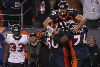 DENVER - DECEMBER 26:  Quarterback Tim Tebow #15 of the Denver Broncos jumps into the arms of his offensive linemen J.D. Walton #50 and Ryan Harris #74 after his game winning six yard bootleg touchdown run in the fourth quarter as free safety Troy Nolan #