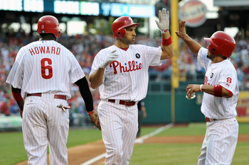 PHILADELPHIA, PA - JULY 26: Raul Ibanez #29 of the Philadelphia Phillies gets congratulated by teammates Ryan Howard #6 and Shane Victorino #8 after hitting a three-run home run during the game against the San Francisco Giants at Citizens Bank Park on Jul