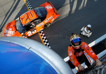 JOLIET, IL - JULY 15:  Tony Stewart, driver of the #20 The Home Depot Chevrolet, climbs the fence to the starters' stand in celebration of winning the NASCAR Nextel Cup Series USG Sheetrock 400 at Chicagoland Speedway on July 15, 2007 in Joliet, Illinois.