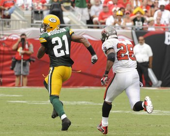 TAMPA, FL - SEPTEMBER 28: Cornerback Charles Woodson #21 of  the Green Bay Packers wrestles a pass away from running back Warrick Dunn #28 of the Tampa Bay Buccaneers at Raymond James Stadium on September 28, 2008 in Tampa, Florida.  Woodson ran for a tou