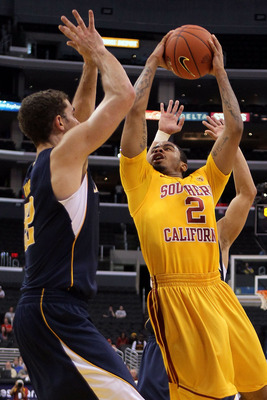 LOS ANGELES, CA - MARCH 10:  Jio Fontan #2 of the USC Trojans goes up for a shot against Harper Kamp #22 of the California Golden Bears in the first half in the quarterfinals of the 2011 Pacific Life Pac-10 Men's Basketball Tournament at Staples Center on