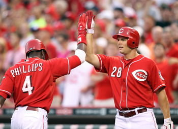 CINCINNATI, OH - JULY 24:  Brandon Phillips #4 of the Cincinnati Reds is congratulated by Chris Heisey #28 after hitting a home run during the game against the Atlanta Braves at Great American Ball Park at Great American Ball Park on July 24, 2011 in Cinc