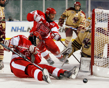 BOSTON - JANUARY 08:  Joe Pereira #6 and Luke Popko #26 of the Boston University Terriers try to get the puck past John Muse #1 of the Boston College Eagles on January 8, 2010 during the Sun Life Frozen Fenway Hockey Game at the Fenway Park in Boston, Mas