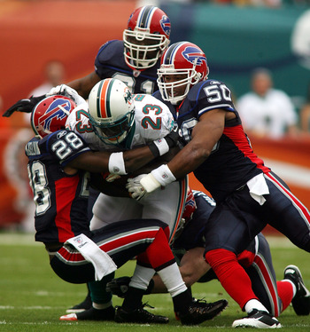 MIAMI, FL - DECEMBER 19:  Running back Ronnie Brown #23 of the Miami Dolphins is upended by cornerback Leodis McKelvin #28 and Akin Ayodele #50 of the Buffalo Bills at Sun Life Stadium on December 19, 2010 in Miami, Florida.  (Photo by Marc Serota/Getty I