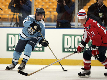Errey dekes a former Capital during the alumni game before the Winter Classic