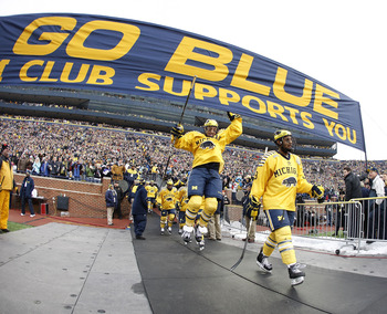 ANN ARBOR, MI - DECEMBER 11:  Lee Moffie #13 of the Michigan Wolverines jumps to the Michigan banner on his way to the ice prior to playing Michigan State at Michigan Stadium on December 11, 2010 in Ann Arbor, Michigan.  (Photo by Gregory Shamus/Getty Ima