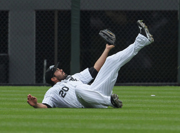 CHICAGO, IL - JULY 27: Carlos Quentin #20 of the Chicago White Sox rolls after making a diving catch in the 9th inning against the Detroit Tigers at U.S. Cellular Field on July 27, 2011 in Chicago, Illinois. The White Sox defeated the Tigers 2-1. (Photo b