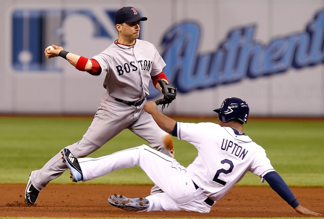ST. PETERSBURG, FL - JULY 16:  Shortstop Marco Scutaro #10 of the Boston Red Sox turns a double play as B.J. Upton #2 of the Tampa Bay Rays tries to break it up during the game at Tropicana Field on July 16, 2011 in St. Petersburg, Florida.  (Photo by J.
