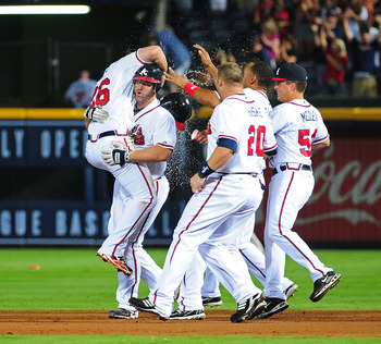 ATLANTA - JULY 27: David Ross #8 of the Atlanta Braves celebrates with teammates after knocking in the game-winning run in the 10th inning against the Pittsburgh Pirates at Turner Field on July 27, 2011 in Atlanta, Georgia. (Photo by Scott Cunningham/Gett