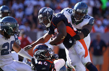 DENVER - SEPTEMBER 19:  Running back Knowshon Moreno #27 of the Denver Broncos is stopped by defensive tackle Brandon Mebane #92 of the Seattle Seahawks at INVESCO Field at Mile High on September 19, 2010 in Denver, Colorado. The Broncos defeated the Seah