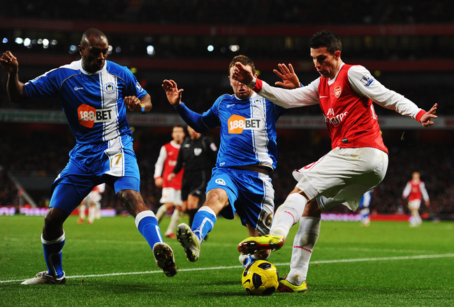 LONDON, UNITED KINGDOM - JANUARY 22:  Robin Van Persie (R) of Arsenal eludes James McArthur (C) and Emmerson Boyce (L) of Wigan Athletic during the Barclays Premier League match between Arsenal and Wigan Athletic at the Emirates Stadium on January 22, 201