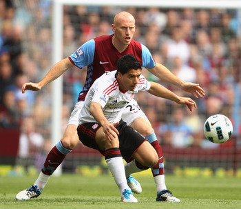 BIRMINGHAM, ENGLAND - MAY 22:  Luis Suarez of Liverpool battles with James Collins of Aston Villa during the Barclays Premier League match between Aston Villa and Liverpool at Villa Park on May 22, 2011 in Birmingham, England.  (Photo by Bryn Lennon/Getty