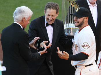 SAN FRANCISCO, CA - APRIL 09:  Cody Ross #13 of the San Francisco Giants receives his World Series ring from Giants owner Bill Neukom (L) and Giants President Larry Baer before the start of the game against the St. Louis Cardinals at AT&T Park on April 9,