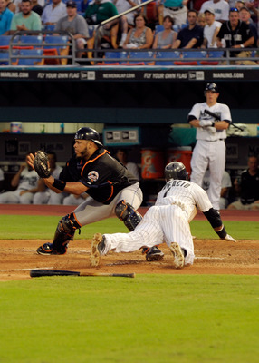MIAMI GARDENS, FL - JULY 22: Emilio Bonifacio #1 of the Florida Marlins slides safely into home plate before the tag of Ronny Paulino #9 of the New York Mets during a game at Sun Life Stadium on July 22, 2011 in Miami Gardens, Florida.  (Photo by Sarah Gl
