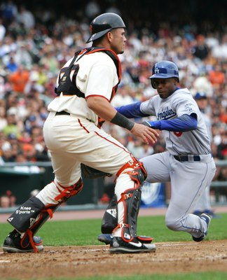 SAN FRANCISCO - SEPTEMBER 30:  Kenny Lofton #6 of the Los Angeles Dodgers scores on a sacrafice fly hit by J.D. Drew as catcher Eliezer Alfonso #50 of the San Francisco Giants waits for the throw on September 30, 2006 at AT&T Park in San Francisco, Califo