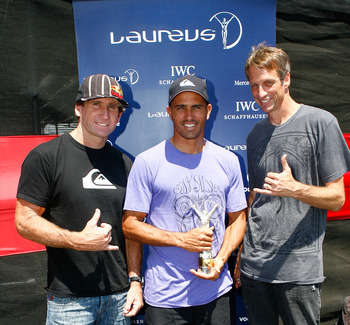 CARSON, CA - AUGUST 2:  Windsurfer Robby Naish (l) and former pro skateboarder Tony Hawk (r) present the 2009 Laureus World Action Sportsperson of the Year Award to pro surfer Kelly Slater (c) during a presentation ceremony at X Games 15 at The Home Depot