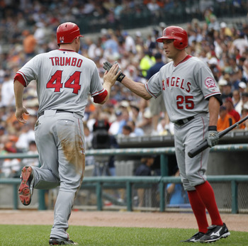 DETROIT - JULY 28:  Mark Trumbo #44  of the Los Angeles Angeles of Anaheim hits a second inning home run and is congratulated by teammate Peter Bourjos #25 during the game against the Detroit Tigers at Comerica Park on July 28, 2011 in Detroit, Michigan.