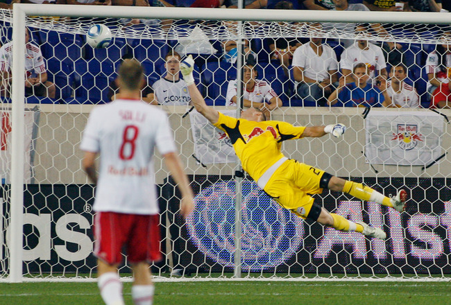 HARRISON, NJ - JUNE 10: Goalkeeper Greg Sutton #24 of the New York Red Bulls makes a save as Jan Gunnar Solli #8 of the New England Revolution looks on against the New England Revolution during the game at Red Bull Arena on June 10, 2011 in Harrison, New