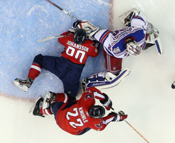 WASHINGTON, DC - APRIL 13:  Marcus Johansson #90 of the Washington Capitals lands in the crease as Henrik Lundqvist #30 of the New York Rangers tends net in Game One of the Eastern Conference Quarterfinals during the 2011 NHL Stanley Cup Playoffs at Veriz