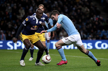 MANCHESTER, ENGLAND - DECEMBER 01:  Adam Johnson of Manchester City competes with Ibrahim Sekagya of FC Salzburg during the UEFA Europa League Group A match between Manchester City and FC Salzburg at the City of Manchester Stadium on December 1, 2010 in M