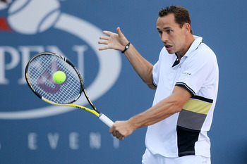 NEW YORK - SEPTEMBER 05:  Michael Llodra of France returns a shot against Tommy Robredo of Spain during the men's singles match on day seven of the 2010 U.S. Open at the USTA Billie Jean King National Tennis Center on September 5, 2010 in the Flushing nei