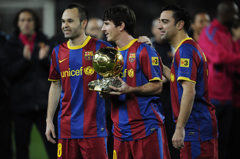 BARCELONA, SPAIN - JANUARY 12:  Lionel Messi of FC Barcelona (C) holds the Ballon d'Or trophy flanked by his teammates Andres Iniesta (L) and Xavi Hermandez prior the Copa del Rey quarter final first leg match FC Barcelona and Betis at Camp Nou on January
