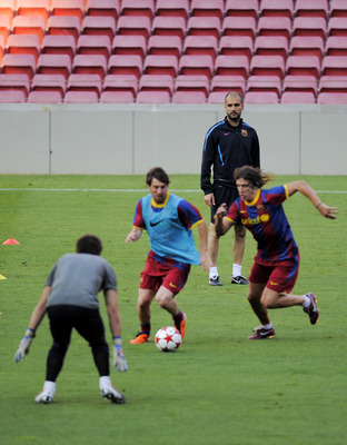 BARCELONA, SPAIN - MAY 23:  Head coach Josep Guardiola of FC Barcelona, (background), follows the action of his players Lionel Messi  (C) and Carles Puyol (R) during the FC Barcelona training session held ahead of next Saturday's UEFA Champions League Fin