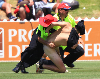 WELLINGTON, NEW ZEALAND - JANUARY 17: A streaker is tackled by security guards during day three of the Second Test match between the New Zealand Blackcaps and Pakistan at Basin Reserve on January 17, 2011 in Wellington, New Zealand. (Photo by Marty Melvil