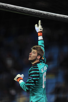 MADRID, SPAIN - DECEMBER 01:  Goalkeeper David de Gea of Atletico Madrid touches the goal post during the Europea League match between Atletico Madrid and Aris Thessaloniki at the Vicente Calderon Stadium on December 1, 2010 in Madrid, Spain.  (Photo by J
