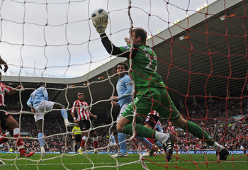 SUNDERLAND, ENGLAND - AUGUST 29: Simon Mignolet of Sunderland saves from Emmanuel Adebayor of Manchester City during the Barclays Premier League match between Sunderland and Manchester City at the Stadium of Light on August 29, 2010 in Sunderland, England