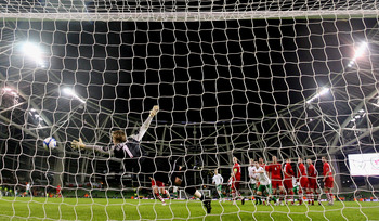 DUBLIN, IRELAND - FEBRUARY 08:  Wayne Hennessey of Wales fails to keep out a free kick from Ireland's Keith Fahey during the Carling Nations Cup match between Republic of Ireland and Wales at Aviva Stadium on February 8, 2011 in Dublin, Ireland.  (Photo b