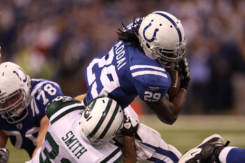 INDIANAPOLIS, IN - JANUARY 08:  Joseph Addai #29 of the Indianapolis Colts runs the ball against Eric Smith #33 of the New York Jets during their 2011 AFC wild card playoff game at Lucas Oil Stadium on January 8, 2011 in Indianapolis, Indiana. The Jets wo