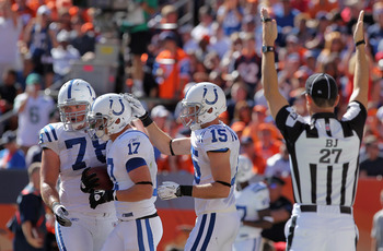 DENVER - SEPTEMBER 26:  Wide receiver Austin Collie #17 of the Indianapolis Colts celebrates his five yard touchdown reception with Mike Pollack #78 and Blair White #15 in the second quarter against the Denver Broncos as back judge Lee Dyer signals at INV