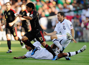 PASADENA, CA - JUNE 25:  Steve Cherundolo #6 of the United States injures his ankle as he collides with teammate Jermaine Jones #13 as they were defending Giovanni Dos Santos #10 of Mexico during the 2011 CONCACAF Gold Cup Championship at the Rose Bowl on