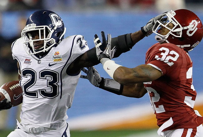 GLENDALE, AZ - JANUARY 01:  Jordan Todman #23 of the Connecticut Huskies stiff arms Jamell Fleming #32 of the Oklahoma Sooners in the second quarter during the Tostitos Fiesta Bowl at the Universtity of Phoenix Stadium on January 1, 2011 in Glendale, Ariz
