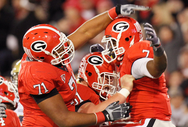ATHENS, GA - NOVEMBER 27:  Cordy Glenn #71 and Ben Jones #61 of the Georgia Bulldogs celebrate with Orson Charles #7 after Charles touchdown against the Georgia Tech Yellow Jackets at Sanford Stadium on November 27, 2010 in Athens, Georgia.  (Photo by Kev