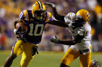 BATON ROUGE, LA - OCTOBER 16:  Russell Shepard #10 of the Louisiana State University Tigers is tackled by London Durham #10 of the McNeese State Cowboys at Tiger Stadium on October 16, 2010 in Baton Rouge, Louisiana.  The Tigers defeated the Cowboys 32-10