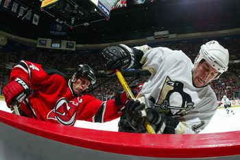 EAST RUTHERFORD, NJ - JANUARY 7:  Scott Stevens #4 of the New Jersey Devils and Ryan Malone #12 of the Pittsburgh Penguins battle for the puck during their game at the Continental Airlines Arena  on January 7, 2004 in East Rutherford, New Jersey. (Photo b