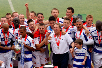 LONDON, ENGLAND - MAY 07:  Neil Warnock (centre right) manager of QPR, Adel Taarabt (centre left) and other members of the squad celebrate with the trophy after winning the npower Championship match between Queens Park Rangers and Leeds United at Loftus R