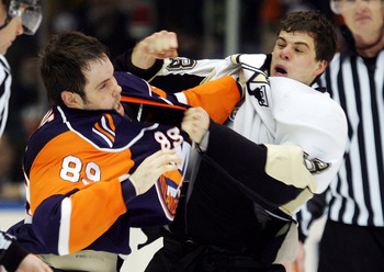 UNIONDALE, NY - FEBRUARY 26:  Mike Comrie #89 of the New York Islanders trades punches with Tyler Kennedy #48 of the  Pittsburgh Penguins during a third period fight on February 26, 2008 at Nassau Coliseum in Uniondale, New York. The Penguins defeated the