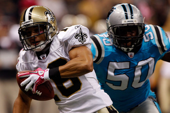 NEW ORLEANS - OCTOBER 03:  Lance Moore #16 of the New Orleans Saints reaches tries to avoid a tackle by James Anderson #50 of the Carolina Panthers at the Louisiana Superdome on October 3, 2010 in New Orleans, Louisiana.  (Photo by Chris Graythen/Getty Im