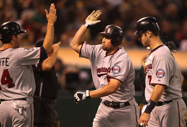 OAKLAND, CA - JULY 29:  Michael Cuddyer #5 of the Minnesota Twins celebrates with Trevor Plouffe #24 and Joe Mauer #7 after hitting a three-run home run against the Oakland Athletics at O.co Coliseum on July 29, 2011 in Oakland, California.  (Photo by Jed