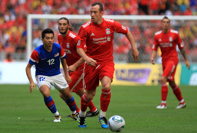 KUALA LUMPUR, MALAYSIA - JULY 16: Charlie Adam of Liverpool dribbles past Amar Rohidan of Malaysia during the pre-season friendly match between Malaysia and Liverpool at the Bukit Jalil National Stadium on July 16, 2011 in Kuala Lumpur, Malaysia. (Photo b